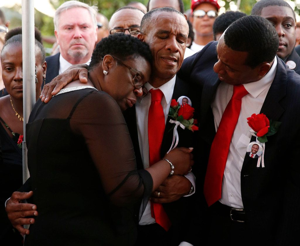 Allison and Bertrum Jean hug as they surrounded by family and friends as their son Botham Jean is buried at Choc Cemetery in Castries, St. Lucia in September 2018. Allison Jean has become a voice for her son since he was shot and killed by Dallas police officer Amber Guyger. Guyger, who was off duty but in uniform, was charged with murder. She has since been fired by the Dallas Police Department. Her trial begins Sept. 23.