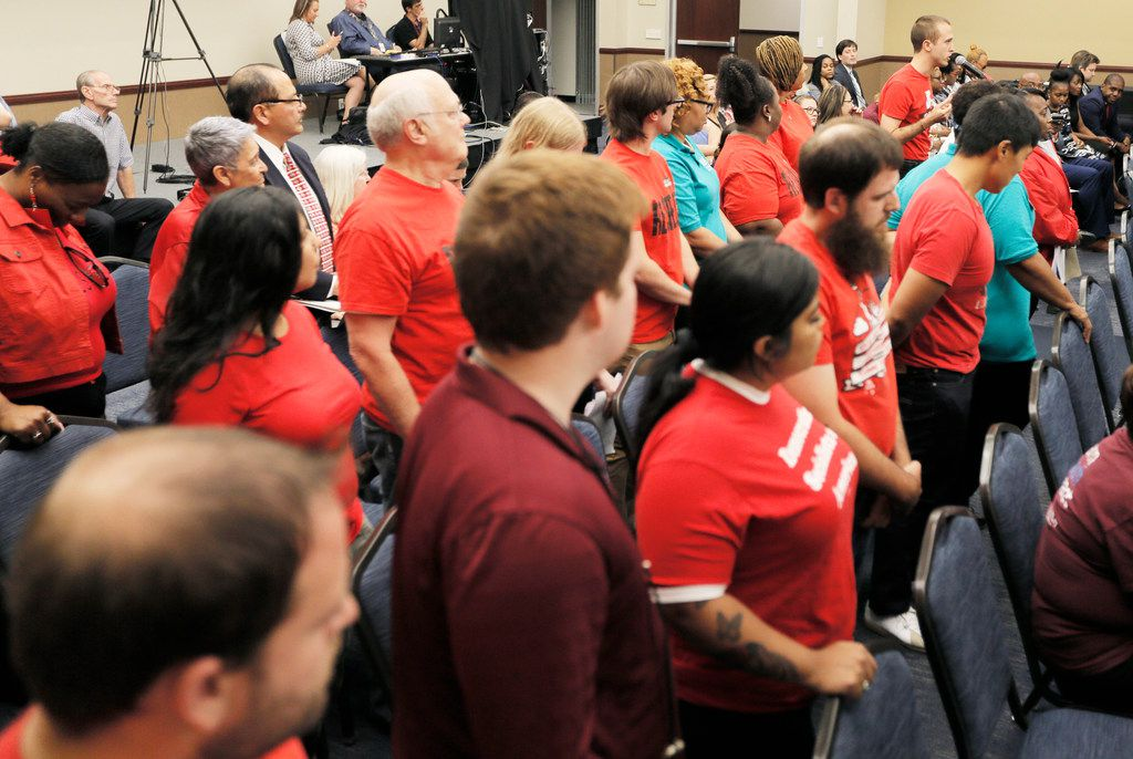 Members of the North Texas Democratic Socialists and American Federation of Teachers union stand as Issac Davis, top right, speaks in favor of a 3 percent raise for Dallas ISD support staff (custodians, office assistants, cafeteria workers, etc.) during a board of trustees meeting on Aug. 23, 2018.