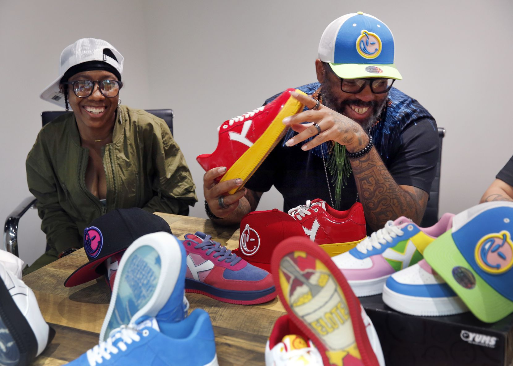 Tex Moton (right), founder and designer of the YUMS streetwear brand, and Juelz look over a collection of sneakers and hats in their new Arlington offices.