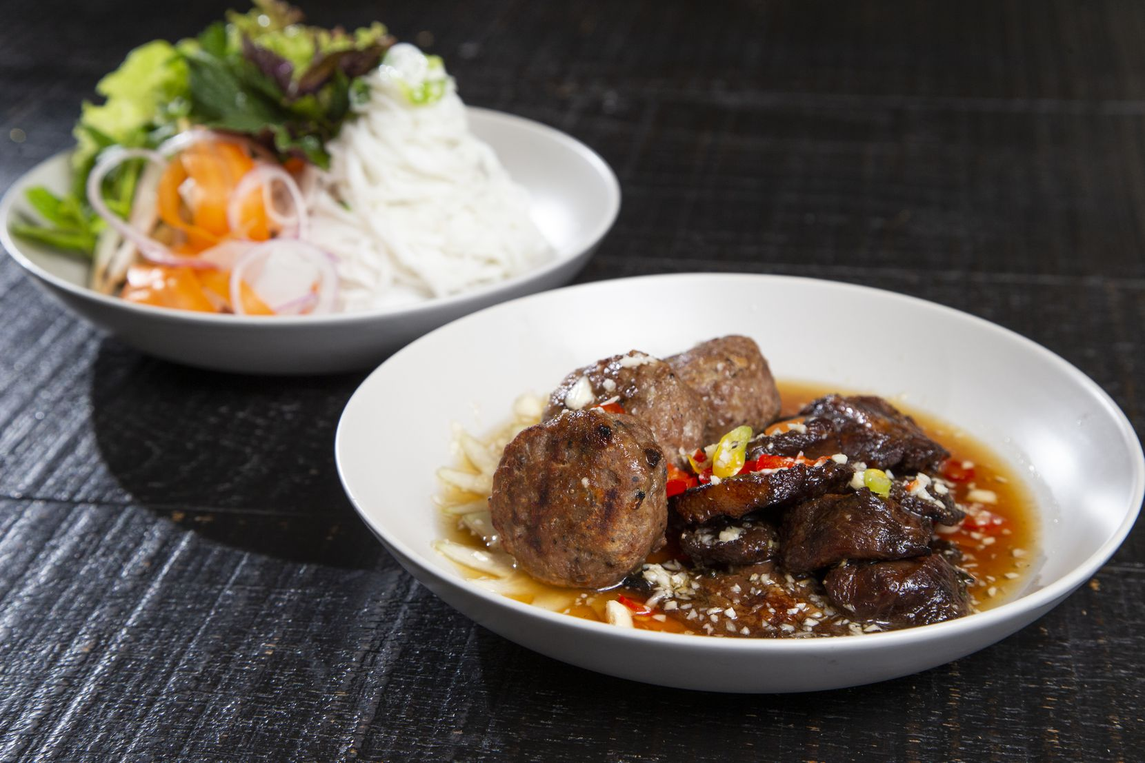 Bun Cha Hanoi, grilled pork patties with grilled sliced pork served with vermicelli noodles with herbs and nước chấm.