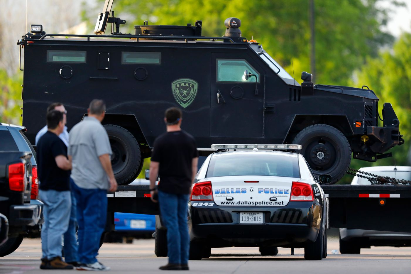 People watch as the Texas Department of Public Safety rolls in heavy duty vehicles to the Home Depot parking lot after two police officers and a civilian were shot by a man outside the home improvement store on April 24, 2018, in Dallas. The officers were critically wounded in the shooting, according to officials.