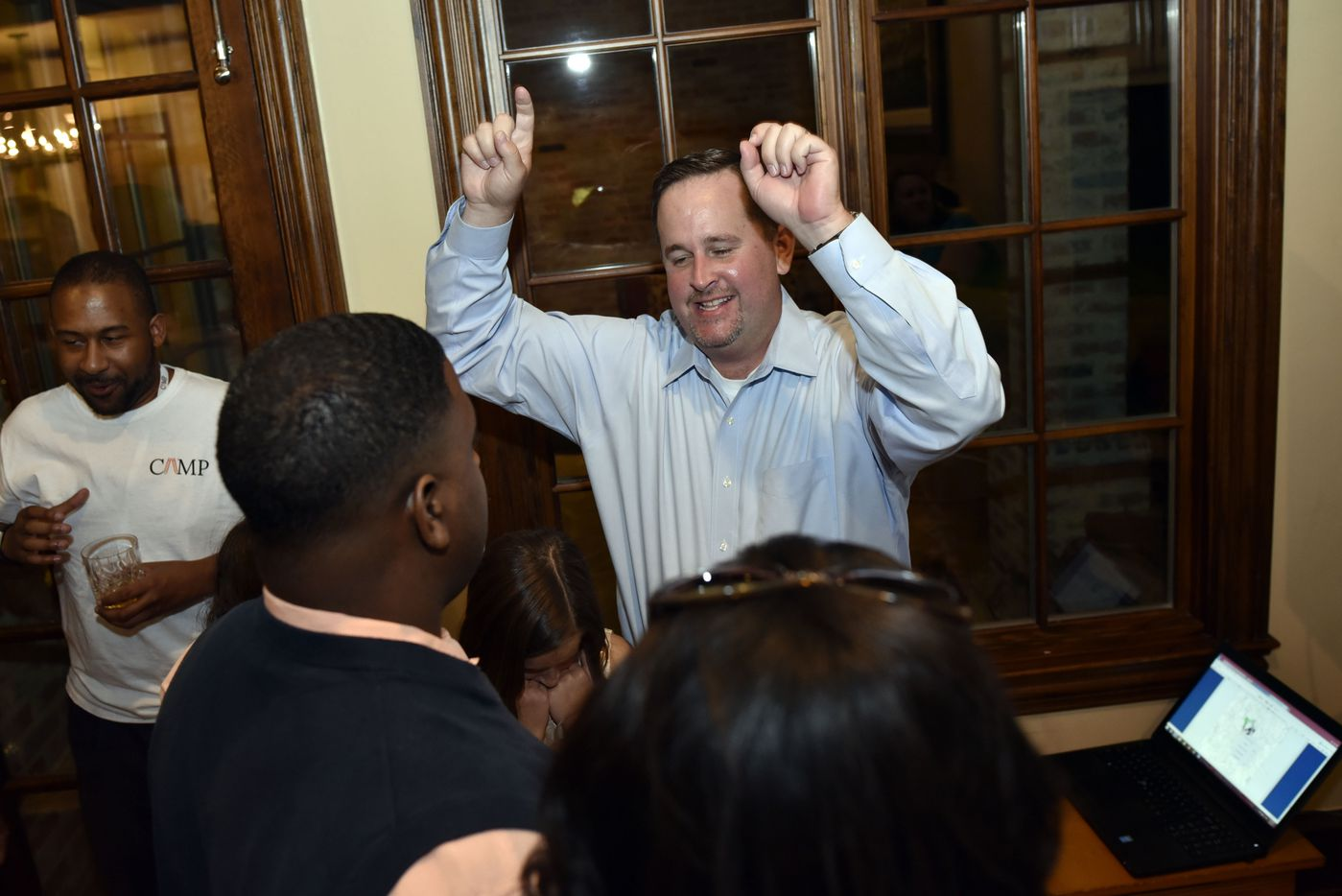 Dustin Marshall, candidate for DISD District 2, reacts after viewing updated numbers during the watch party.