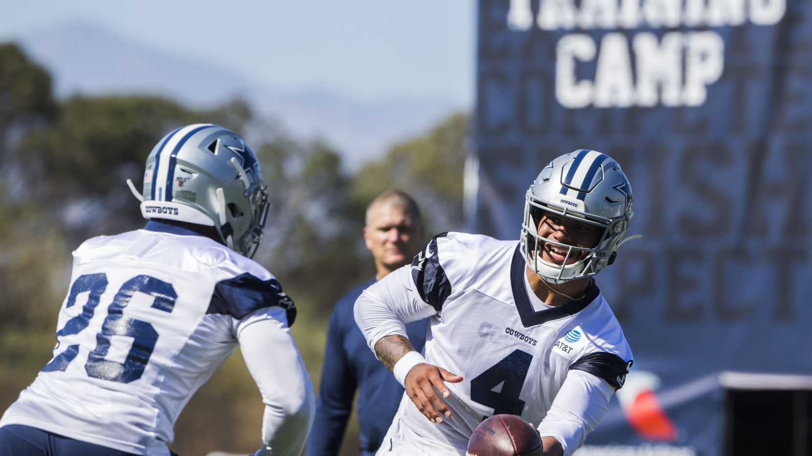 FILE — Dallas Cowboys quarterback Dak Prescott (4) and Darius Jackson (26) during an afternoon practice at training camp in Oxnard, California on Saturday, July 27, 2019.  The coronavirus pandemic has forced the Cowboys to begin their 2020 training camp at their own facility for the first time in franchise history.