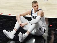 Dallas Mavericks center Kristaps Porzingis sits on the court after a foul during the second half of an NBA playoff basketball game against the LA Clippers at Staples Center on Saturday, May 22, 2021, in Los Angeles.