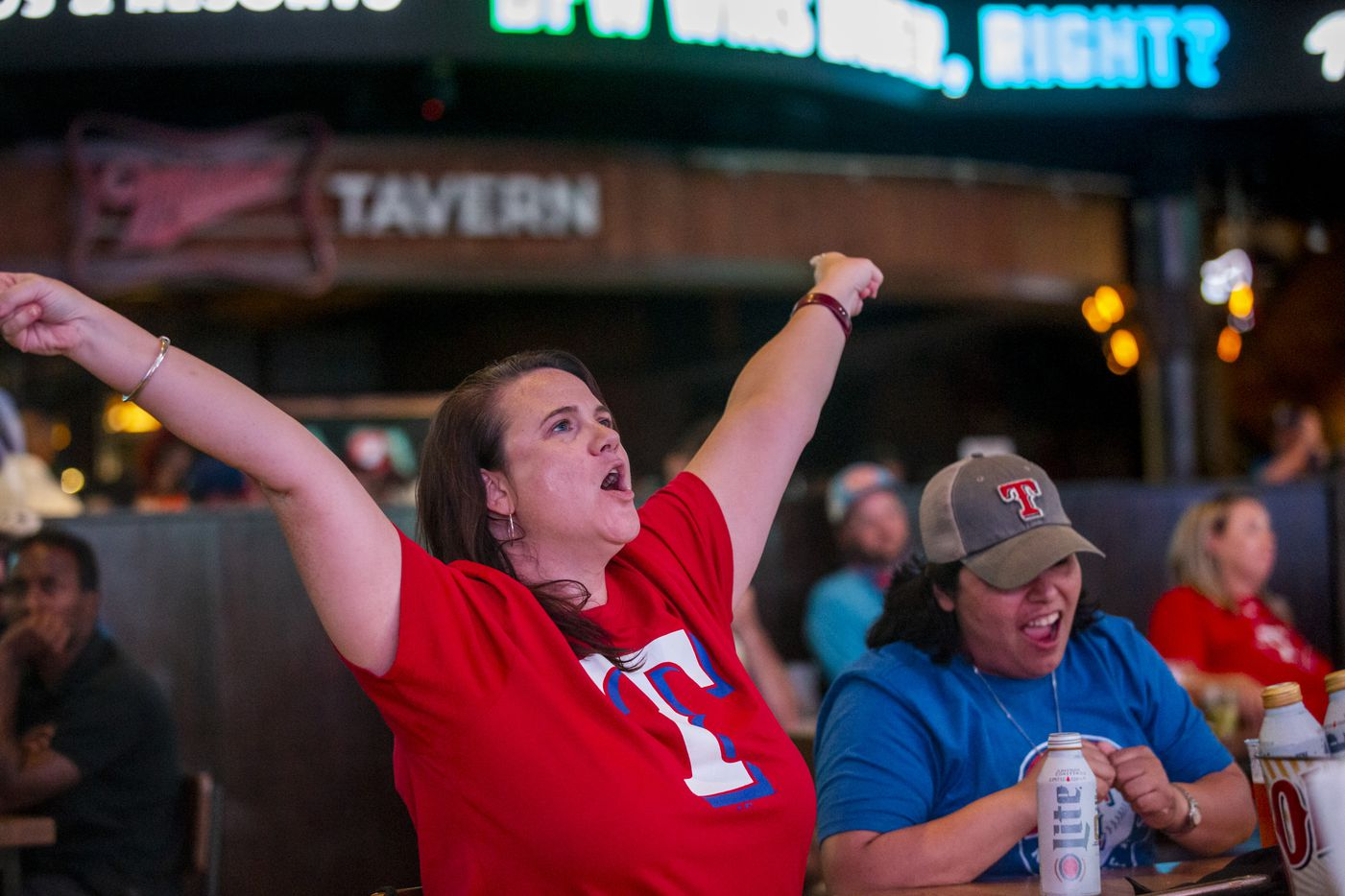 From left, Christen Rogoski, from Dallas and Christi Mava, from Strawn, Texas, cheer with fans as the Texas Rangers near their win during the opening day game of their season at Texas Live! in Arlington, Texas, on Friday, July 24, 2020. The Rangers beat the Colorado Rockies 1-0 at the new Globe Life Field stadium, but fans had to watch on televised screens outside due to the ongoing pandemic. (Lynda M. Gonzalez/The Dallas Morning News)