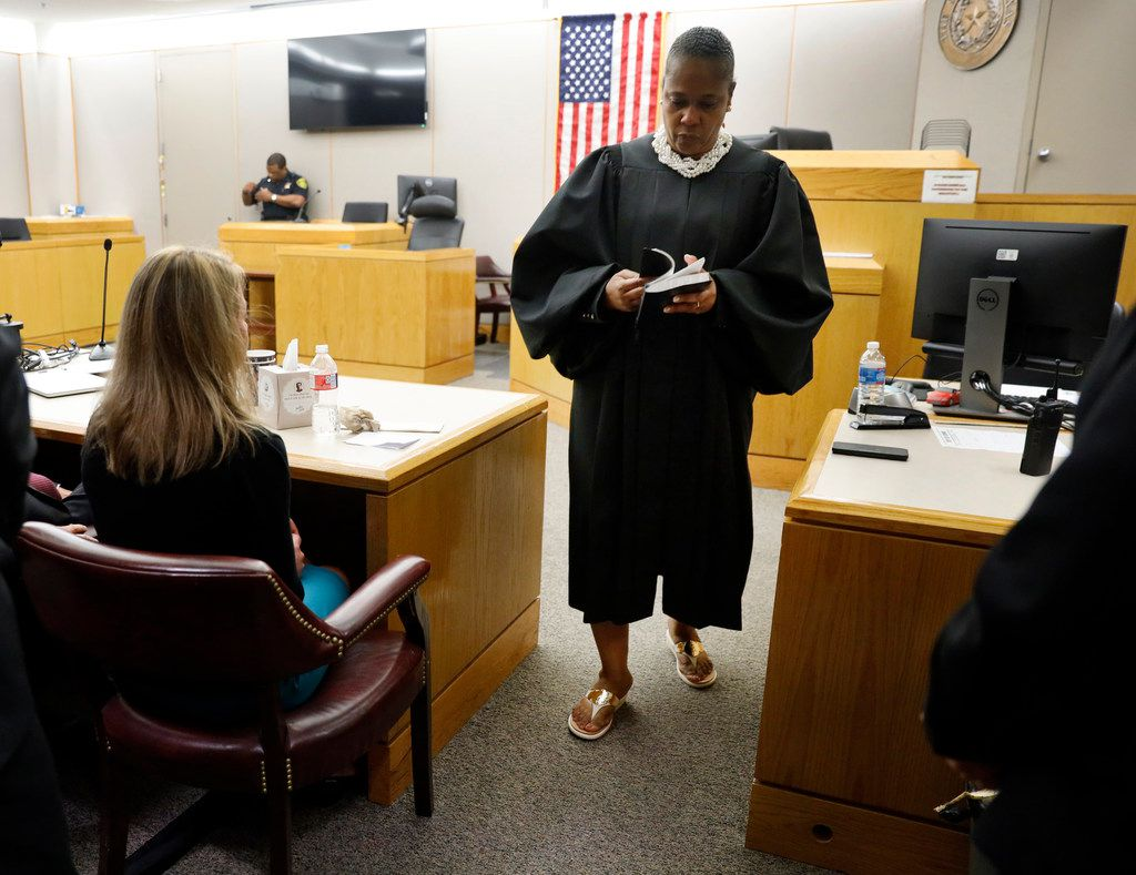 Judge Tammy Kemp opens a Bible to John 3:16 before giving it to Amber Guyger. Kemp gave her one of her own Bibles and some encouragement to do something with her life following the 10-year sentence at the Frank Crowley Courts Building in Dallas, Wednesday, October 2, 2019. Fired Dallas police Officer Amber Guyger was found guilty of murder by a 12-person jury. Guyger shot and killed Botham Jean, an unarmed 26-year-old neighbor in his own apartment last year. She told police she thought his apartment was her own and that he was an intruder.