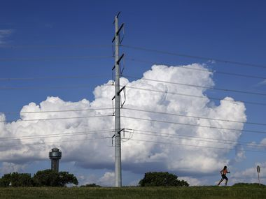 A runner on the Trinity River levee passes a large electrical transmissions line near downtown Dallas, Wednesday, June 30, 2021. (Tom Fox/The Dallas Morning News)