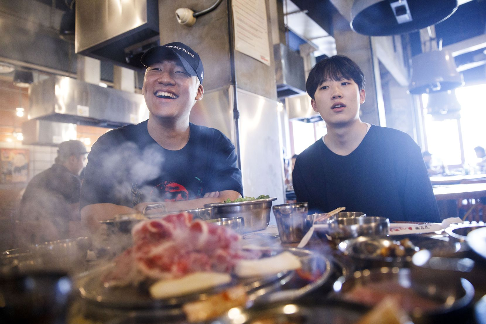 OGE, sitting in Los Angeles' Koreatown, laugs while friend Jeon Kyoung-Min, right, looks on.