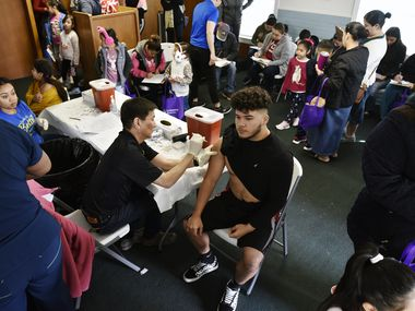 Dallas County health department director Philip Huang gave a flu vaccine to Armando Sanchez, 18, during a health and safety fair at Pleasant Grove Christian Church in Dallas on Jan. 25, 2020.