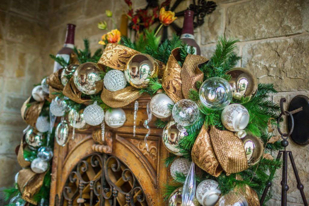 A garland with white and gold ornaments adorns a wine closet tucked under a covered porch.
