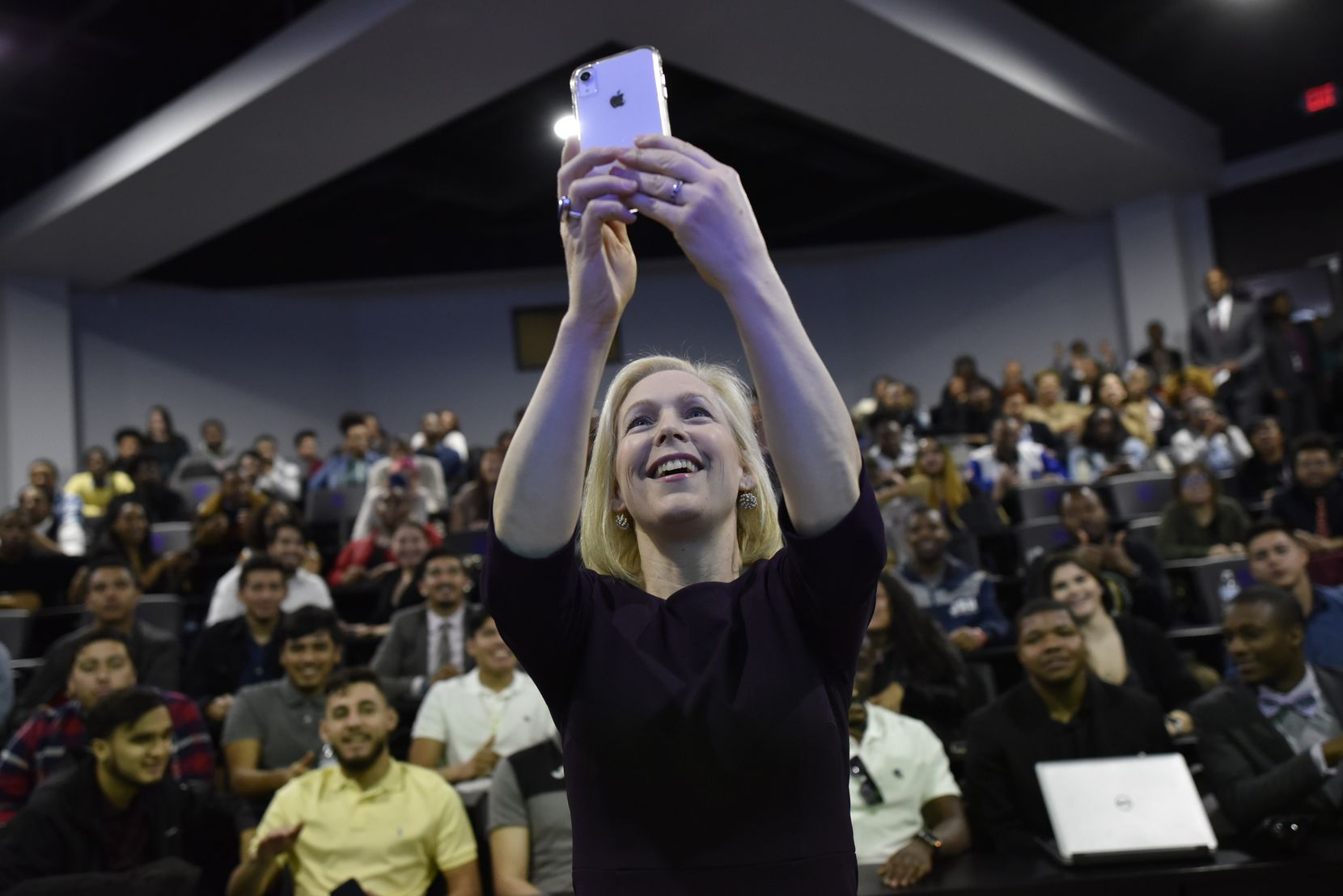 Senator Kirsten Gillibrand holds her phone as she takes a selfie video with students from Paul Quinn College in Dallas, Wednesday,  Feb. 20, 2019. Senator Gillibrand made her first visit to Texas as a presidential candidate visiting the historically black college on Wednesday and the Ann Richards School for Young Women Leaders the following day.