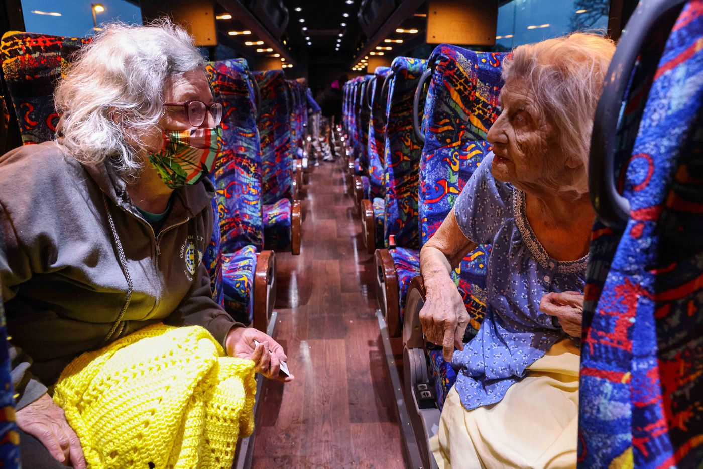 Gloria Sanders, 76, and her mother Maria Barajas, who is 100 years old and has dementia, look at each other as they sit at the bus that serves as a warming center at Pleasant Oaks Recreation Center to spend the night on Wednesday, February 18, 2021 in Dallas.