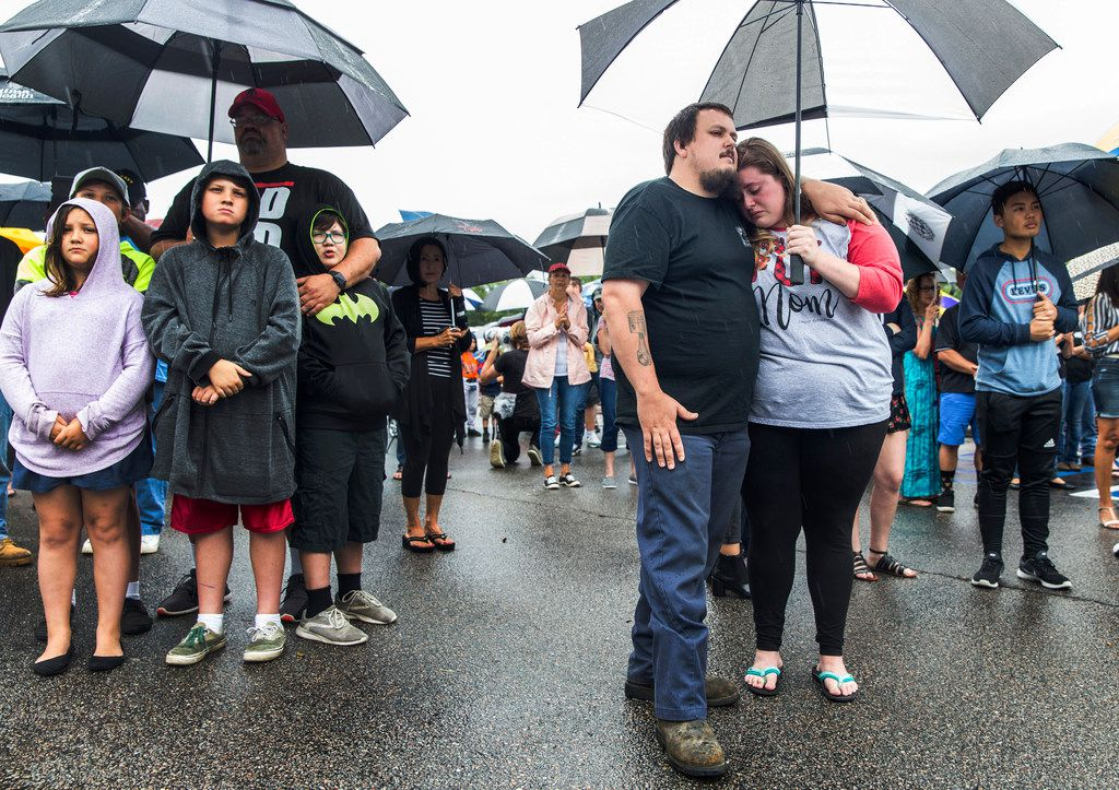Anthony Moore, center, and his fiancée Kaitlyn Mitchell, comfort each other during the prayer vigil at Strawbridge Marketplace, in response to a shooting at a municipal building in Virginia Beach, Va., Saturday, June 1, 2019. A longtime city employee opened fire at the building Friday before police shot and killed him, authorities said. (Daniel Sangjib Min/Richmond Times-Dispatch via AP)