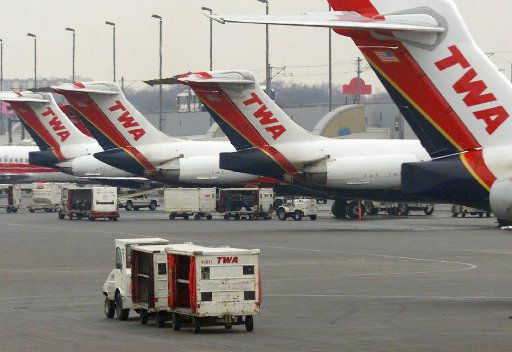 A Trans World Airline baggage cart crosses the tarmac behind a line of TWA jets Monday, Jan. 8, 2001 at Lambert International Airport, TWA's main hub, in St. Louis.  (AP Photo/Tom Gannam)