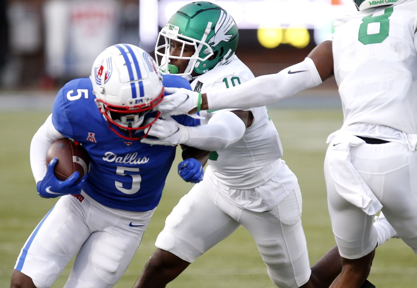 Southern Methodist Mustangs wide receiver Danny Gray (5) gets a double face mask from North Texas Mean Green defensive back Makyle Sanders (10) and North Texas Mean Green defensive back John Davis Jr. (8) during the first half as SMU hosted UNT at Ford Stadium in Dallas on Saturday, September 11, 2021. (Stewart F. House/Special Contributor)