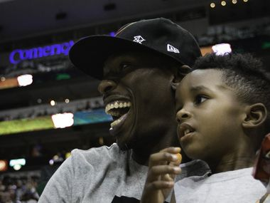 Josh Howard and his son watch the Big 3 Basketball Tournament at the American Airlines Center in Dallas on Sunday, July 30, 2017.