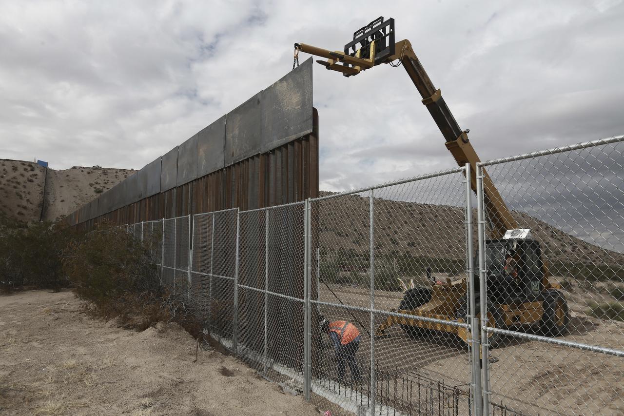 En noviembre del 2016, unos trabajadores levantan una barda más alta entre la frontera entre México y Estados Unidos entre los pueblos de Anapra, México y Sunland Park, Nuevo México. (AP/CHRISTIAN TORRES)