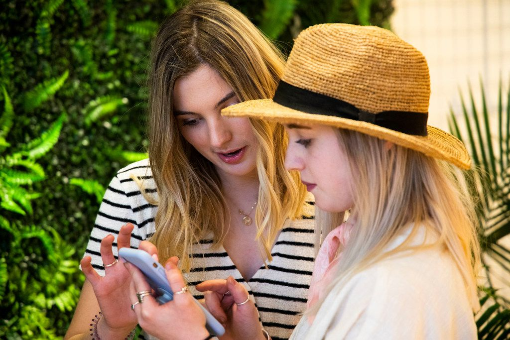 Ella Givens and Ally Jacobs look at their pictures at the Snap151 in Dallas on Friday, April 5, 2019. Snap151 is an interactive photo studio. (Shaban Athuman/Staff Photographer)