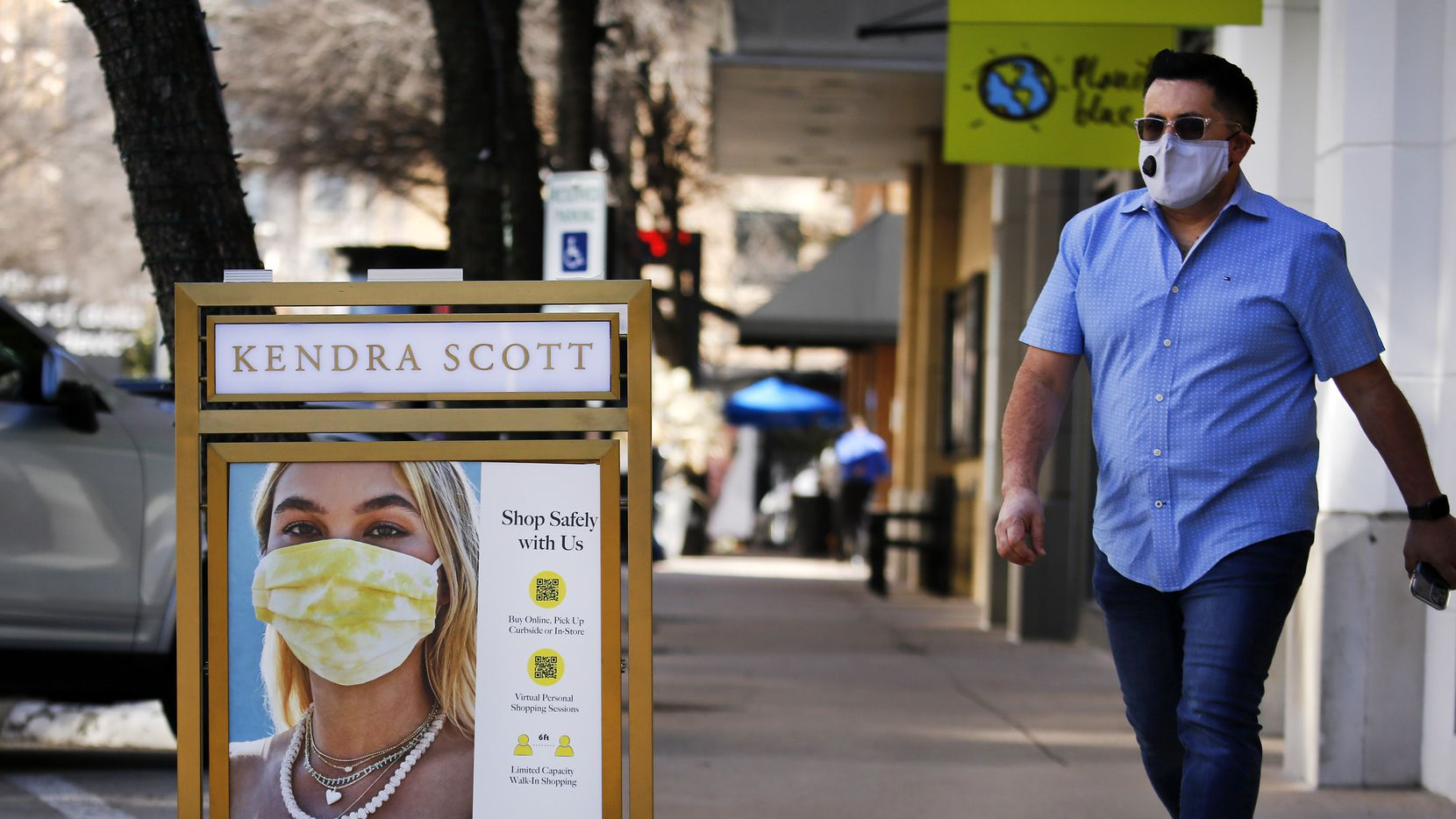 A man walks past a COVID practices sign outside the Kendra Scott store at the West Village in Dallas, Tuesday, March 2, 2021. Upon the one-year anniversary of the COVID-19 pandemic, Texas Governor Greg Abbott announced he plans to end the statewide mask mandate. He also plans on reopening the State of Texas to all businesses.