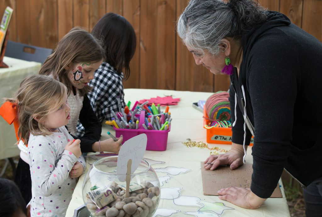 Ofelia Faz-Garza helps Ruby Shearer, 5, create a holiday ornament at a holiday bazaar at the CocoAndre Chocolatier in Oak Cliff on Nov. 24, 2018.