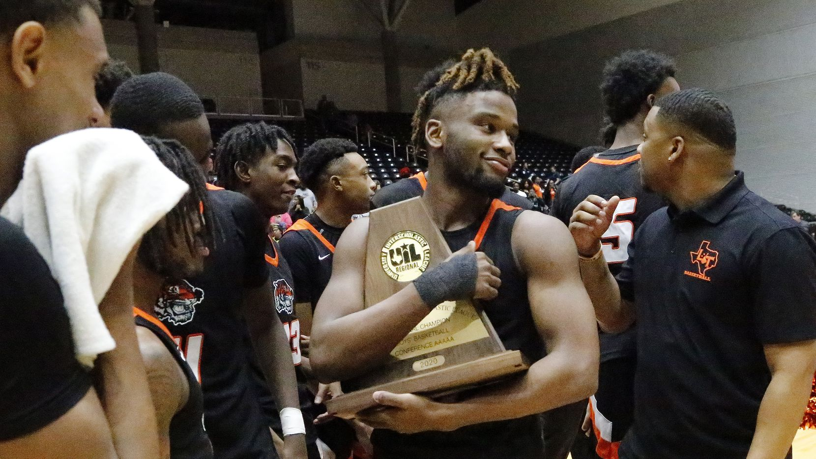 Lancaster High School guard Mike Miles (1) checks out the trophy after the win as Kimball High School played Lancaster High School for the Class 5A Region II championship at the Curtis Colwell Center in Garland on Saturday, March 7, 2020.