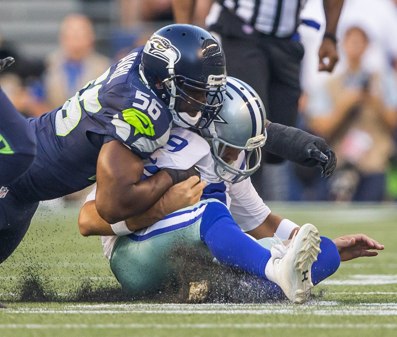 Cliff Avril knocks Dallas quarterback Tony Romo out of the game with this sack on the third play of the game Thursday.  The Dallas Cowboys played the Seattle Seahawks in preseason football Thursday, August 25, 2016 at CenturyLink Field in Seattle. Romo sustained a broken bone in his back when he was hit from behind by Seattle's Cliff Avrill and slid awkwardly on the third play of a preseason game. (Dean Rutz/The Seattle Times)