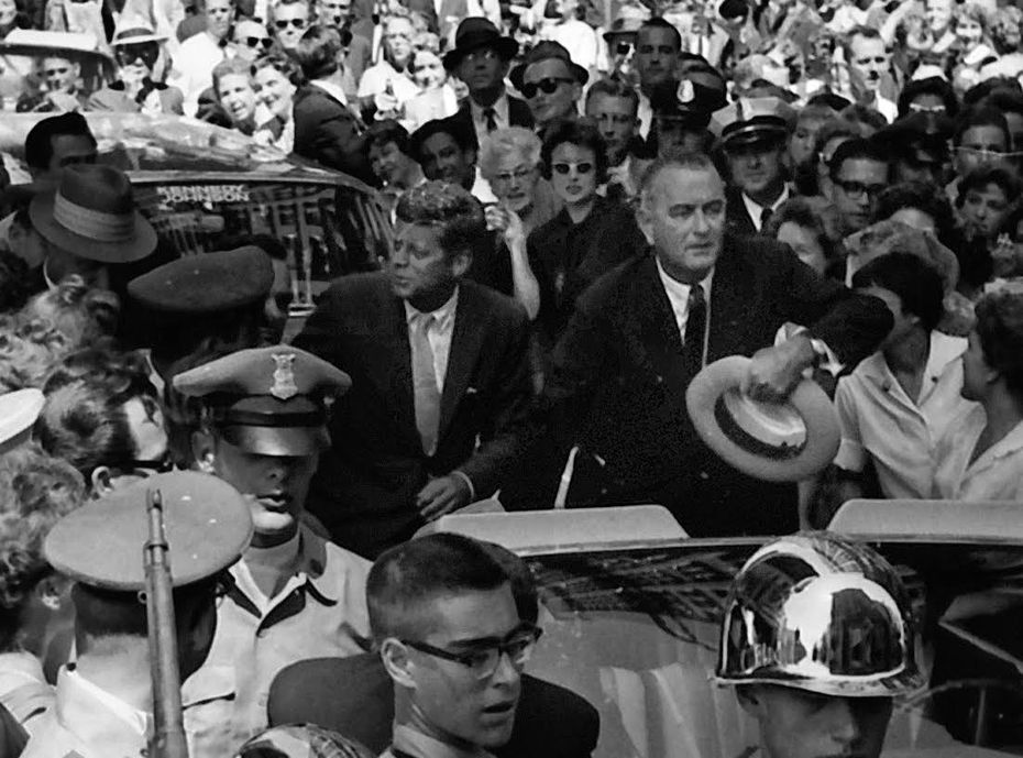 LBJ motions for a path through the 175,000 spectators as the motorcade slows to a crawl at the Mobil Building.