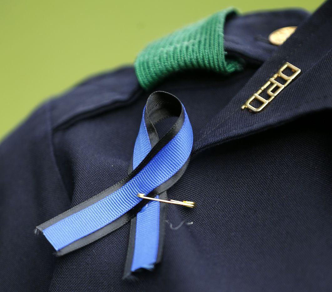 A Dallas Police officer wears a blue ribbon during the Tribute 7/7 memorial event at Dallas City Hall Plaza in Dallas, Friday, July 7, 2017.