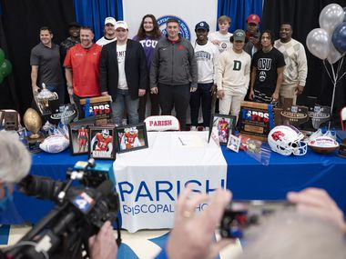 Parish Episcopal head football coach Daniel Novakov, center, stands with members of his football team as they declared to play for universities during National Signing Day, on Wednesday, Feb. 02, 2021 at Parish Episcopal School in Dallas.