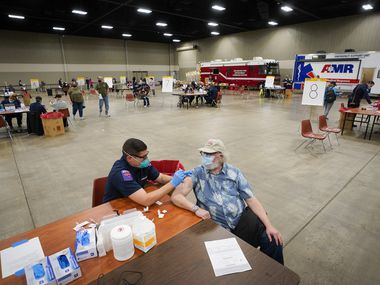 Joe McKay receives the Moderna COVID-19 vaccine from Arlington firefighter Derek O'Neill at the Esports Stadium Arlington & Expo Center on Tuesday, Jan. 5, 2021, in Arlington. The Tarrant County Public Health (TCHP) vaccination program is being implemented by the Arlington Fire Department as part of the city's mass vaccination effort.