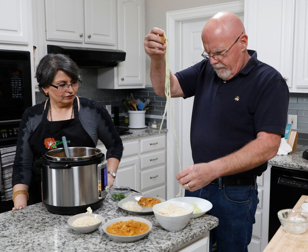 Urvashi Pitre, left, watches her husband, Roger Gorman, place spiralized cucumber noodles on a plate at their home in Keller.