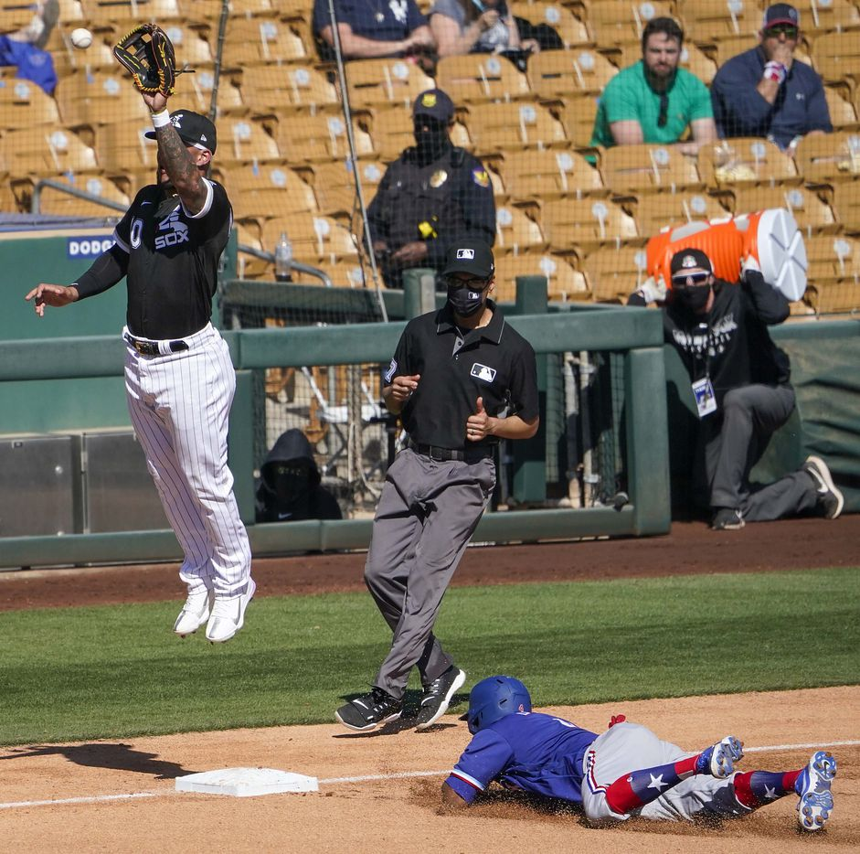 Chicago White Sox third baseman Yoan Moncada  leaps for a high throw as Texas Rangers designated hitter Khris Davis steals third base during the fourth inning of a spring training game at Camelback Ranch on Tuesday, March 2, 2021, in Phoenix, Ariz.