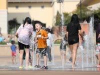 Matthew Ramírez, de 4 años, y su familia de Dallas se refrescan en la fuente de agua de The Harbor Rockwall Texas, el 5 de julio de 2021.