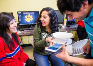 Eighth-grade students Dayanara Torres (left), 14, and Jaydaa Alamaari, 13, react as computer science and networking teacher Mevlut Kaymaz tests a homemade speaker at Harmony School of Business in Dallas. (Ashley Landis/Staff Photographer)