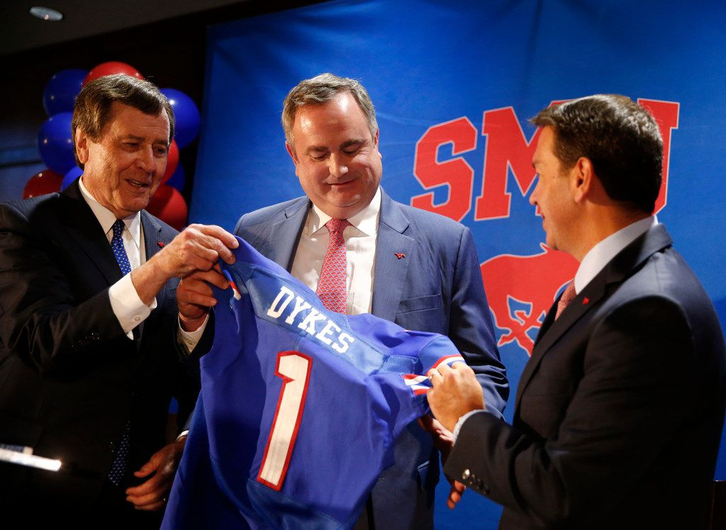 SMU president Gerald Turner (left) and athletic director Rick Hart (right) hand new SMU football coach Sonny Dykes his jersey at The Miller Event Center at SMU in Dallas on Dec. 12, 2017.  (Nathan Hunsinger/The Dallas Morning News)