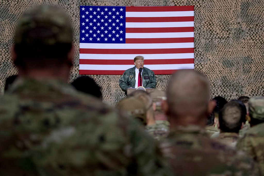 President Donald Trump speaks to members of the military at a hangar rally at Al Asad Air Base, Iraq, on Dec. 26, 2018. He tells troops serving in Iraq that he got them their first pay raise in 10 years and it's a big one. No, and not exactly.