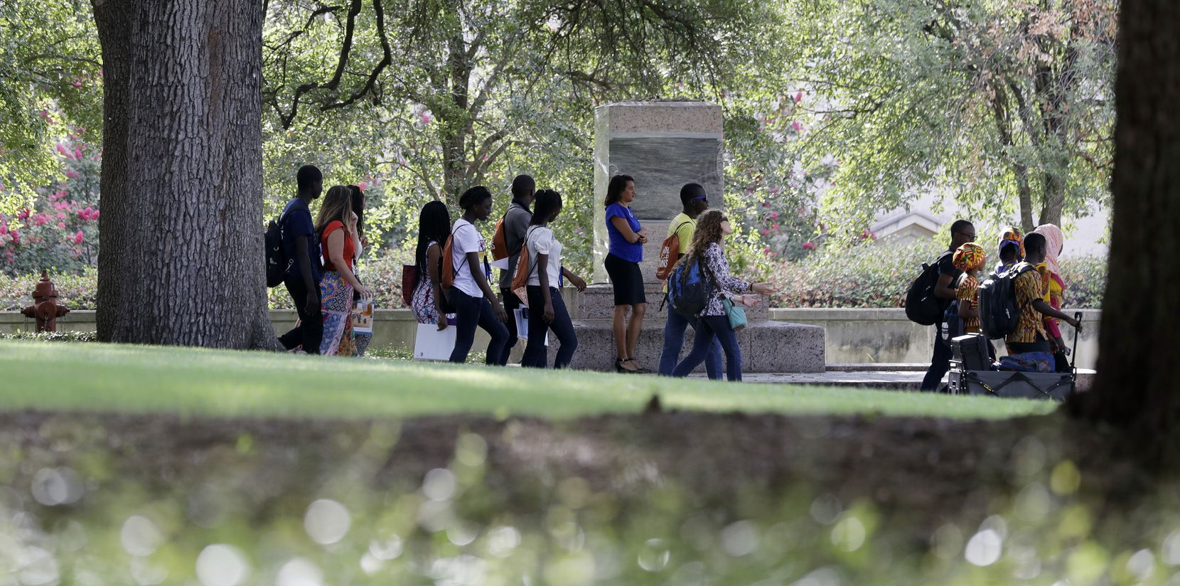 Students pass a pedestal wrapped in plastic that had hosted a statue of Confederate Postmaster General John H. Reagan which was removed from the University of Texas campus early Monday morning, Aug. 21, 2017, in Austin, Texas.