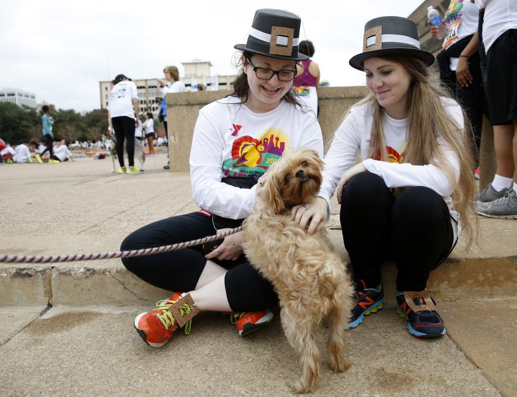 Mara Lipow (left) and Lauren Levine pet a dog named Bella at the 2015 Dallas YMCA Turkey Trot in downtown Dallas.