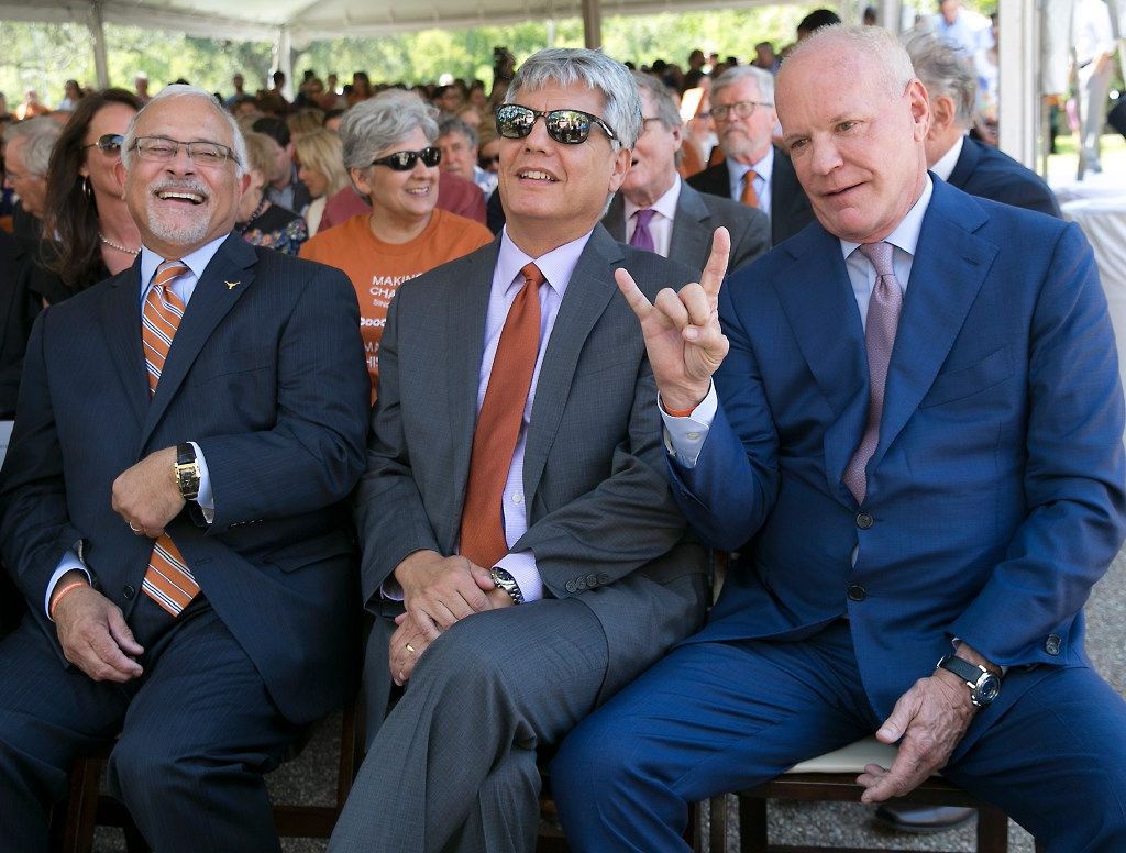 """University of Texas System Regent Steve Hicks, right, puts up his Horns in the sign of a """"Hook 'Em""""  before a celebration ceremony where he announced a gift of $25 million to the School of Social Work in front of the school on campus Wednesday afternoon September 6, 2017. At left is Dean Luis Zayas of the School of Social Work, and at center is UT resident Greg Fenves."""