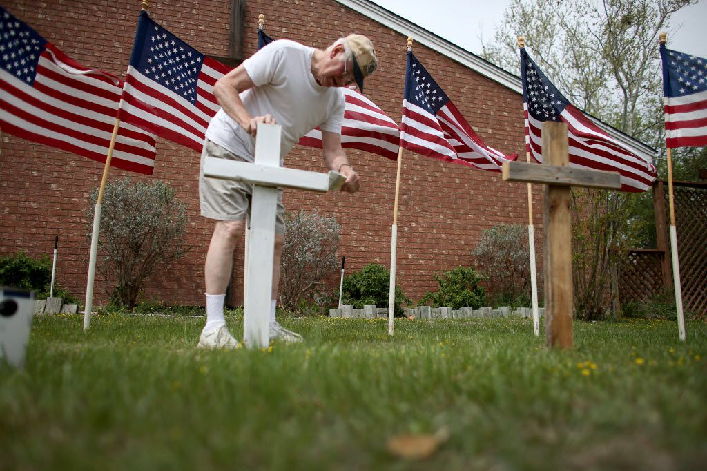 KILLEEN, TX - APRIL 03:  Bob Gordon paints a cross placed in front of 16 American flags as he helps build a memorial in front of Central Christian Disciples of Christ church for the victims of yesterdays shooting at Fort Hood on April 3, 2014 in Killeen, Texas. Iraq war veteran, Ivan Lopez, is reported to be the shooter that claimed three lives and wounded 16 more before taking his own life at Fort Hood.  (Photo by Joe Raedle/Getty Images) 04042014xNEWS