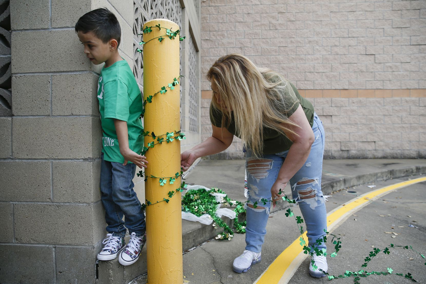 With her son Joel Guerrero's, 6, left, help Veronica Gutierrez, right, mother of Destiny Rangel who was best friends with Emily Bingabing, who was killed outside a Walmart in Far North Dallas in late January, decorates a memorial near the location of the homicide on Saturday, Feb. 22, 2020 in Dallas. Rangel says they plan to continue decorating the location once a month. (Ryan Michalesko/The Dallas Morning News)