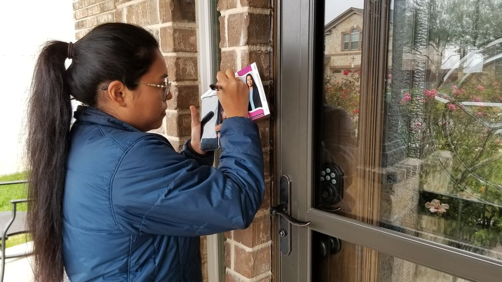 Congressional candidate Jessica Cisneros leaves a flyer at a home in Live Oak, Texas, on Feb. 19, 2020, as she campaigns to unseat Rep. Henry Cuellar, D-Laredo, in the March 3 Democratic primary.