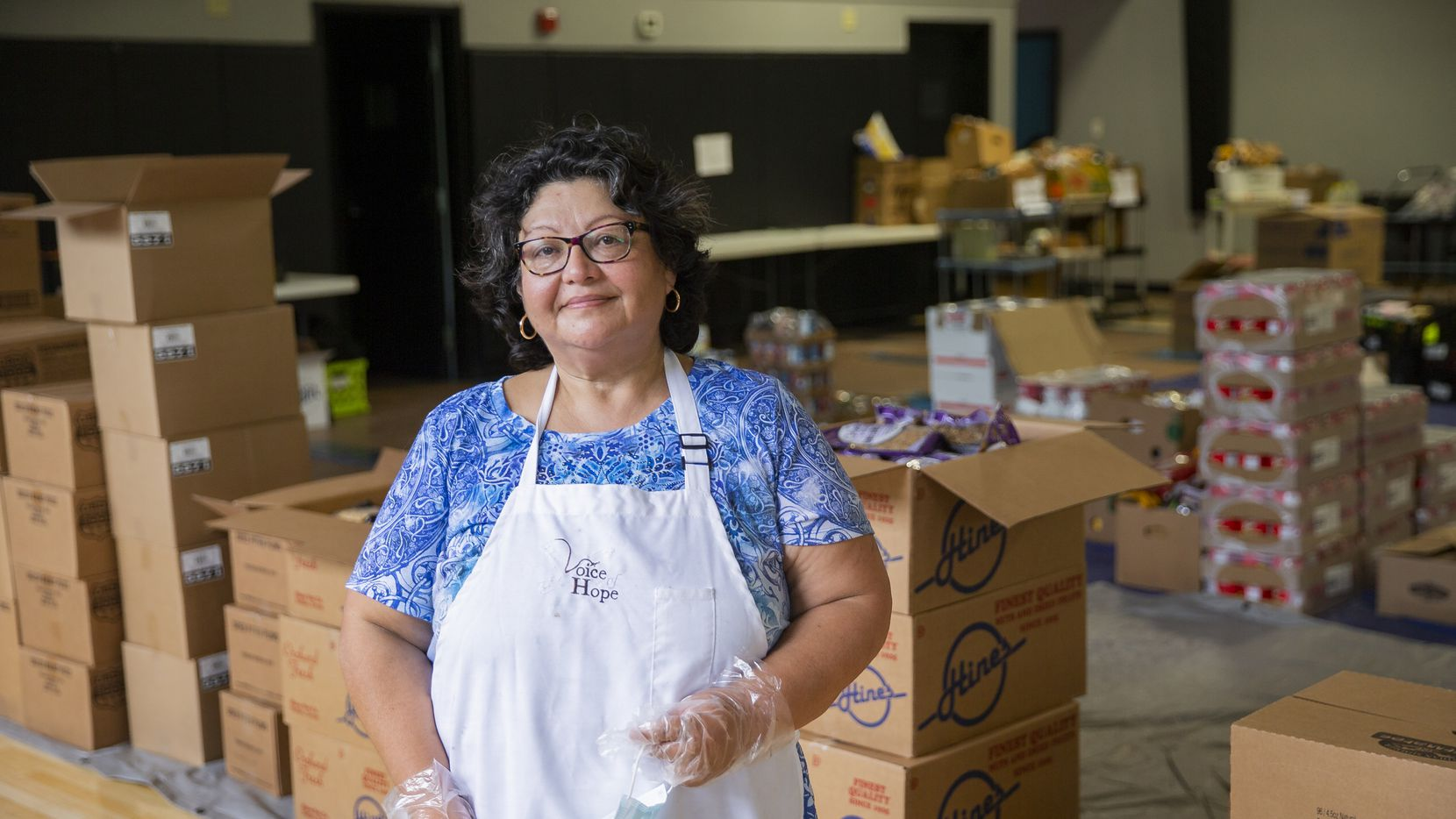 Debbie Solis, a lifelong resident of West Dallas and director of family and community services at Voice of Hope Ministries, stands amid the provisions that the nonprofit is providing to those in need during the coronavirus pandemic.