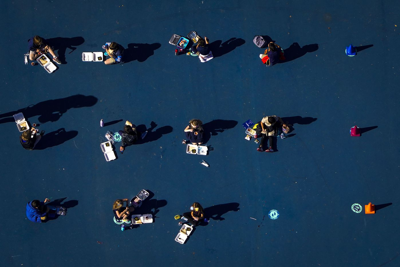 Socially-distanced children eat lunch on the playground at Lakewood Elementary School on Thursday, Dec. 10, 2020, in Dallas, Texas.
