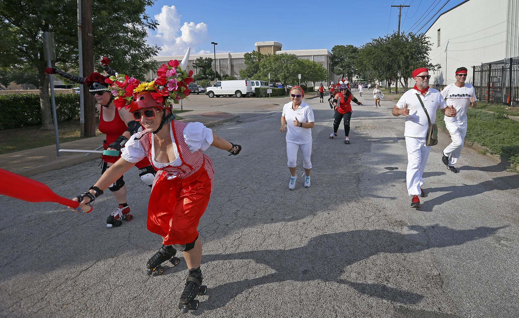 """Members of the Dallas Derby Devils roller-skated past runners on McKee Street during the """"Cedars Running of the Bulls"""" event in Dallas on July 16, 2017. The bulls were played by the Derby Devils, who chased the runners on the less-than-half-mile run."""
