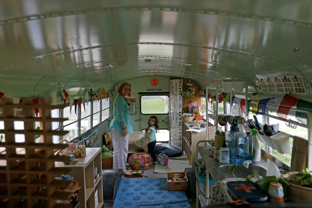 Jennifer Stuart (left) helps Inez Beltran, 3, prepare to eat snacks at Seed Preschool, a school inside a bus at Twelve Hills Nature Center in Dallas. (Jae S. Lee/The Dallas Morning News)