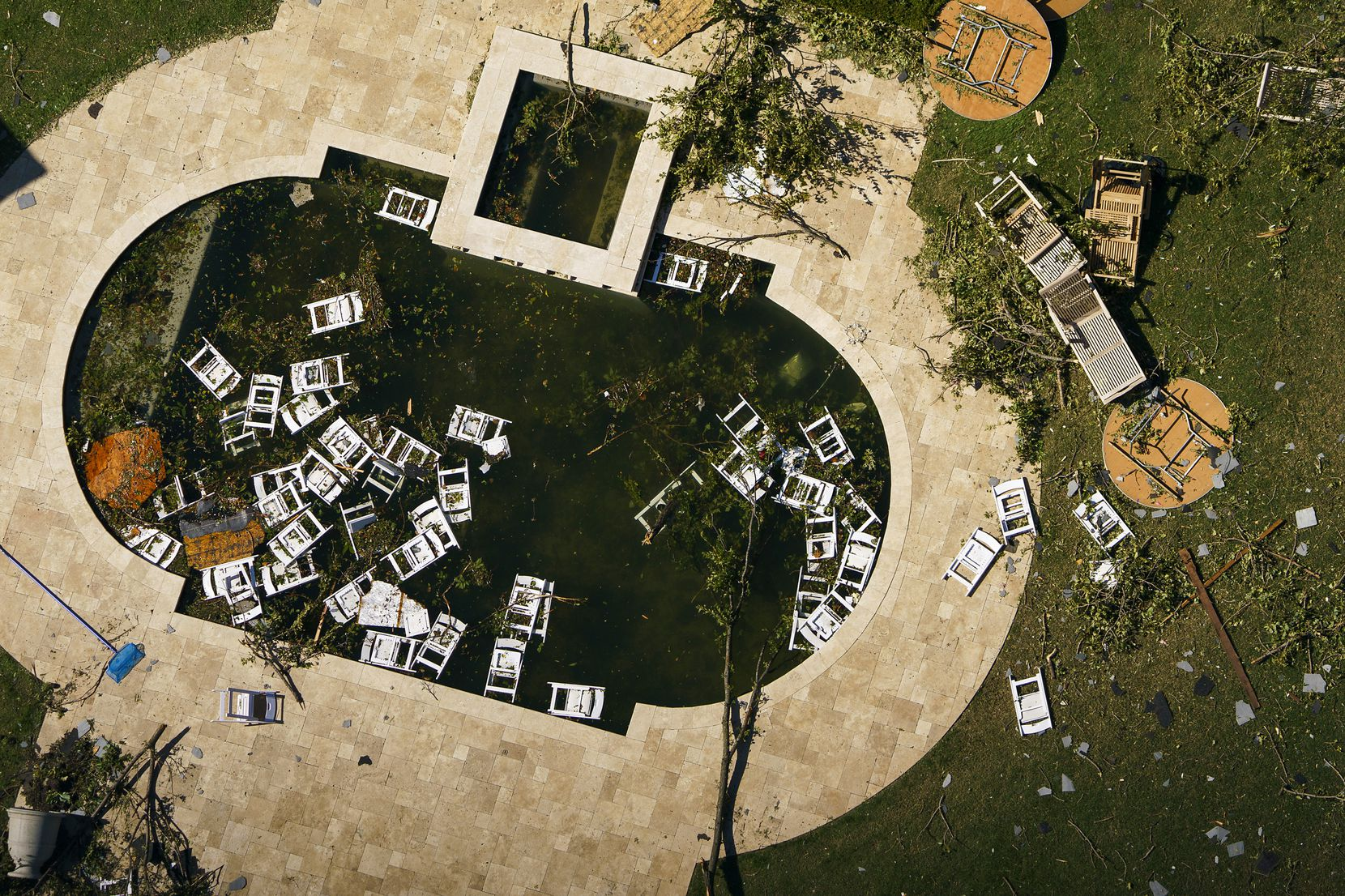 Chairs float in a backyard pool with debris from tornado damage near Walnut HIll Lane and Mash Lane on Monday, Oct. 21, 2019, in Dallas.