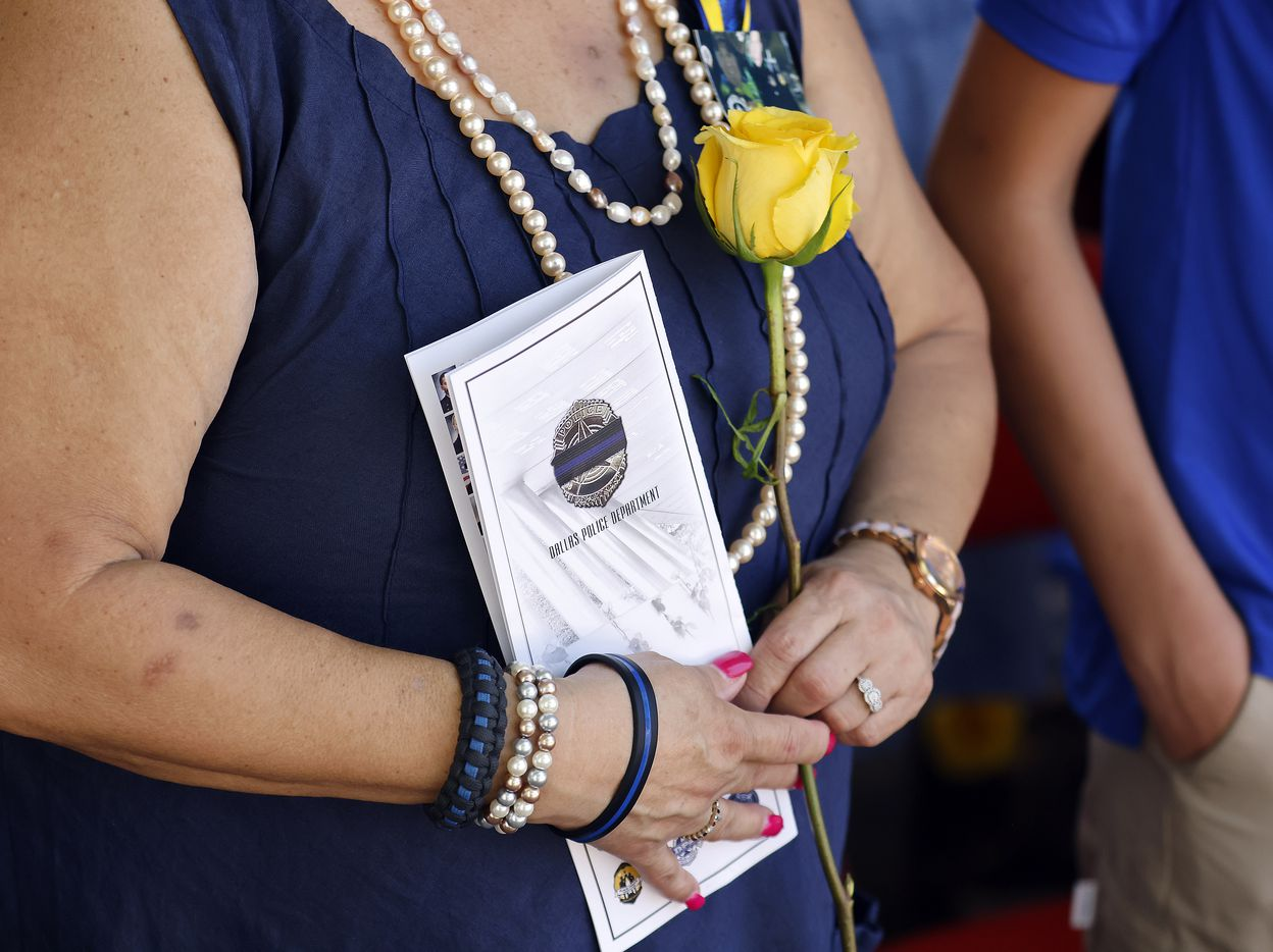 """A family member of fallen Dallas police officer Patricio """"Patrick"""" Zamarripa clutches a yellow rose and program during the annual Police Memorial Day in which the Department honored officers who died in the line of duty at the Dallas Police Memorial in downtown Dallas, Wednesday, July 7, 2021.  Zamarripa was one of the officers remembered on the 5th anniversary of the July 7th ambush. (Tom Fox/The Dallas Morning News)"""