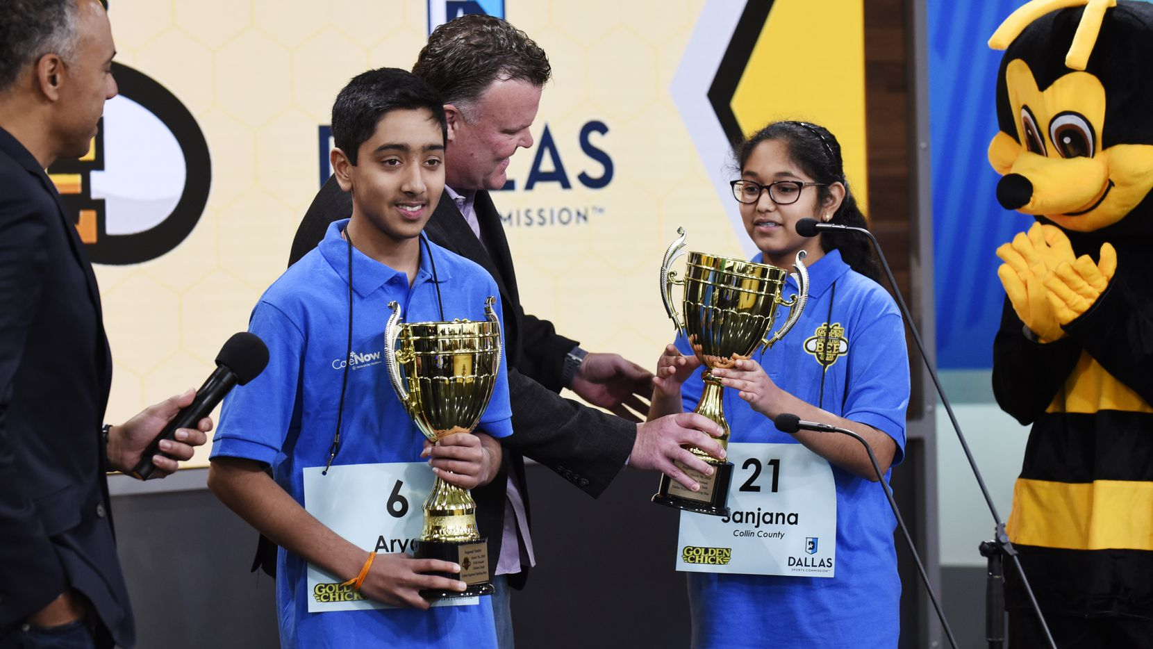 Golden Chick President Jim Stevens hands Dallas Regional Spelling Bee championship trophies to Arya Reddyvari (left) and Sanjana Kota, both of Collin County. The middle-school students shared the championship after 26 rounds of competition.