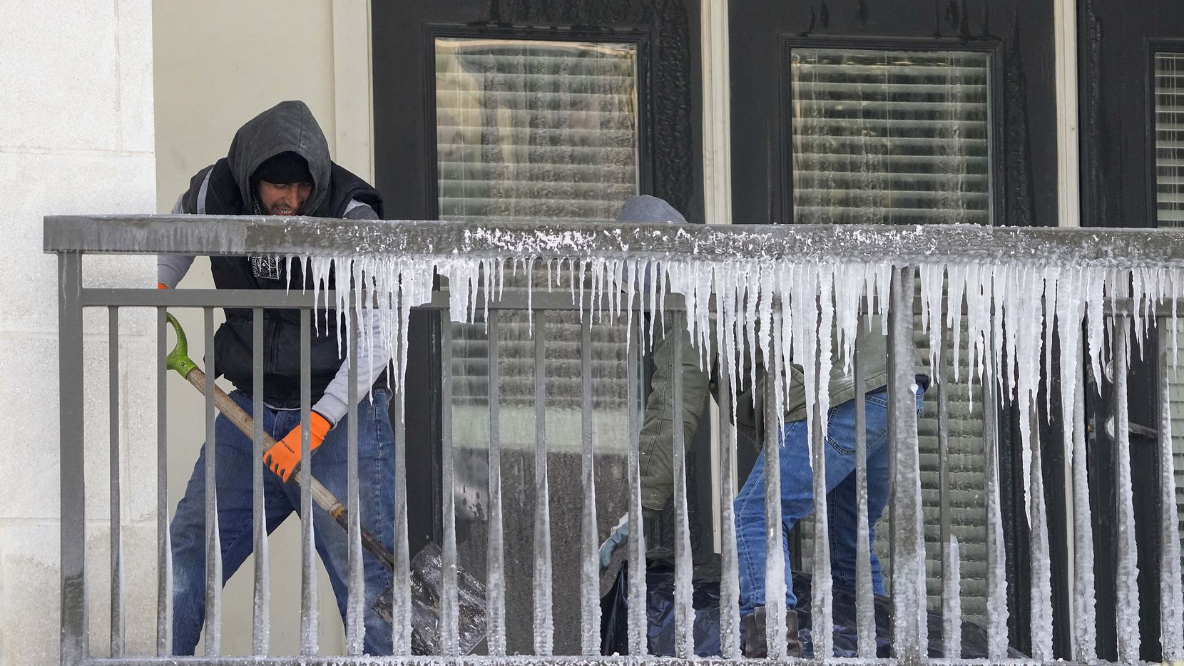 Workers clear debris from a balcony covered in icicles in the Camden Victory Park apartments after a winter storm brought snow and continued freezing temperatures to North Texas. Crews were gutting apartments that were flooded by a broken piped for fire sprinklers.  (Smiley N. Pool/The Dallas Morning News)